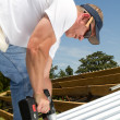 Roofer Fastening Metal Roof - Stock Photo