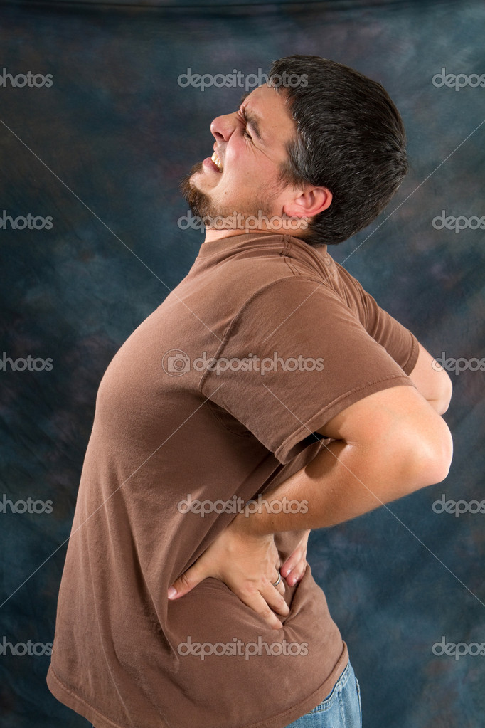 Man with back pain massages his back trying to relieve his backache. — Stock Photo #3177170