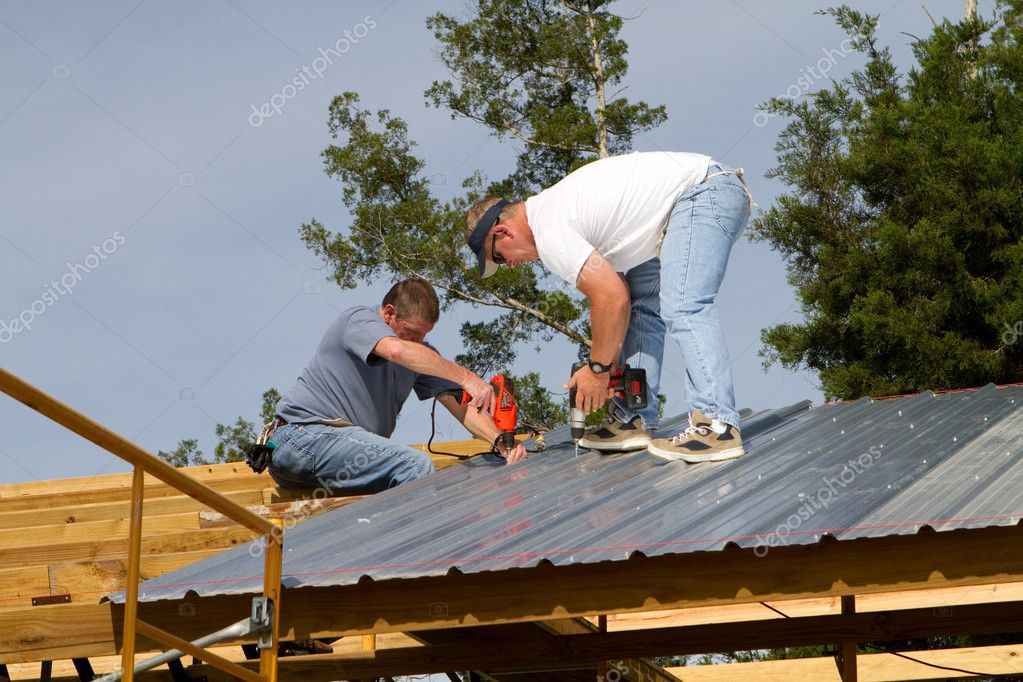 Two construction workers attach sheet metal to wood rafters of a barn with electric and battery powered screw guns.  — Stock Photo #3192093