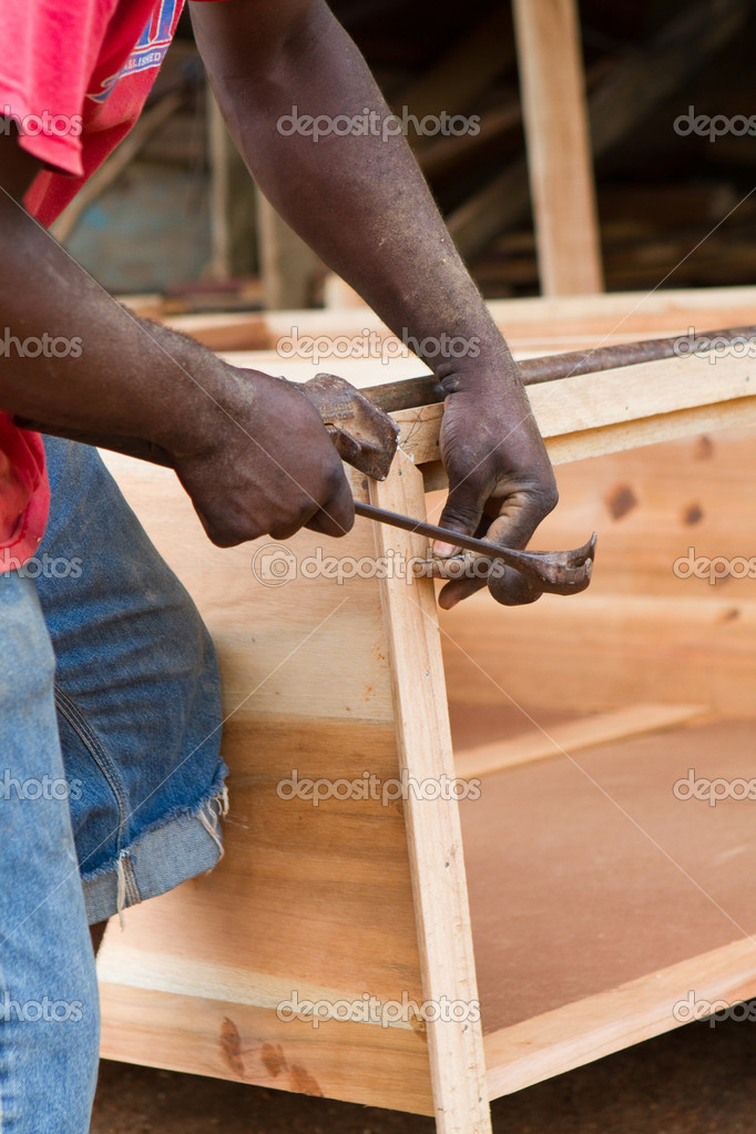 Black man uses hammer and nail to build a dresser chest out of cedar in Jamaica. — Stock Photo #3616974