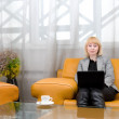 Blonde woman with laptop in comfort hall - Stock Photo