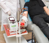 A donor in an armchair donating blood at hemotransfusion station — Stock Photo