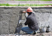 A worker applies plaster to a wall, outdoors — Stock Photo