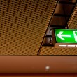 Illuminated green emergency exit sign — Stock Photo #3779381