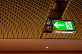 Illuminated green emergency exit sign — Stok fotoğraf