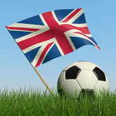 Soccer ball in the grass and flag of Great Britain. — Stock Photo