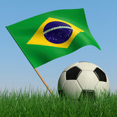 Soccer ball in the grass and the flag of Brazil — Stock Photo