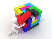 Mannen met een kubus opgebouwd uit blokken. puzzel — Stockfoto
