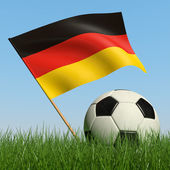 Soccer ball in the grass and flag of Germany — Stock Photo