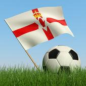 Balón de fútbol en el césped y la bandera de irlanda del norte. — Foto de Stock