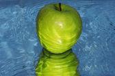 Green apple on water — Stock Photo