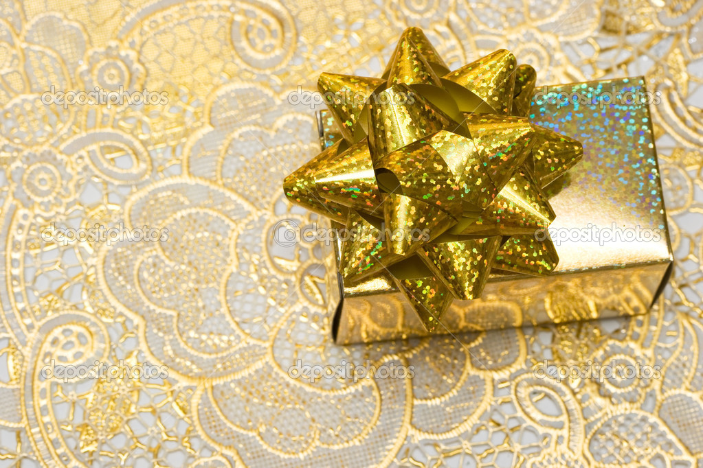 Gold gift box with bow on beautiful background — Stock Photo #2793982