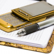 Stock Photo: Mobile phone with pen and notebook