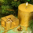 Gold festive candle and present with tree — Stock Photo