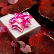 Gift box with red flowers — Stock Photo
