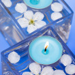 Candle with spring flowers — Stock Photo