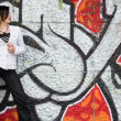 Girl near the wall with graffiti - Stock Photo