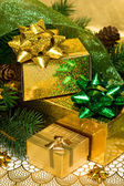 Gold gift boxes with Christmas tree — Stock Photo