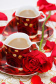 Red cup of coffee with roses — Stock Photo