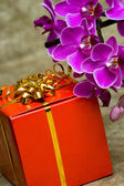 Gift box with purple orchid — Stock Photo