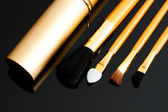 Cosmetic brushes on black background — Stock Photo