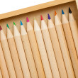 Many colored pencils in row over white background - Stock Photo