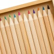 Many colored pencils in row over white background — Stock Photo