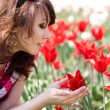 Tender girl in the garden with tulips — Stock Photo