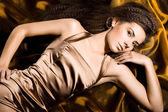 Sexy fashionable woman in golden dress — Stock Photo
