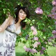 Stock Photo: Tender girl in the garden with lilac
