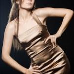 Elegant fashionable woman in golden dress — Stock Photo