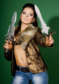 Woman with daggers on green background — Stock Photo