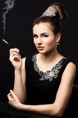 Beautiful woman smokes a cigarette — Stock Photo