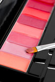 Palette of lipsticks with cosmetic brush — Stockfoto
