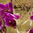 Glass with champagne and orchid — Stock Photo