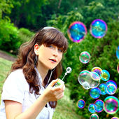 Young girl blowing soap bubbles in spring green — Stock Photo