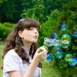 Royalty-Free Stock Photo: Young girl blowing soap bubbles in spring green