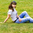 Smile teen sitting in spring park - Stockfoto