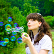 Young girl blowing soap bubbles in spring green - Stockfoto