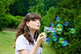 年轻的姑娘在春天绿色吹肥皂泡泡 — 图库照片