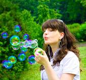 Giovane ragazza soffiando bolle di sapone in primavera verde — Foto Stock