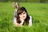 Young adult beautiful girl lying in grass — Stock Photo