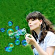 Girl blowing bubbles in spring time — Stock Photo