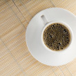 Cup of coffee over bamboo — Stock Photo