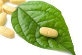 Macro of pills over green leaf — Stock Photo