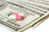 Capsule pills over dollar banknotes — Stock Photo