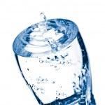 Water splashing into glass isolated — Stock Photo