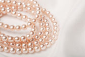 Pearl necklace over white silk — Stock Photo