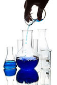 Hand pouring blue chemical liquid into flask isolated — Stock Photo