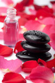 Spa stones, essential oil and rose petals — Stock Photo